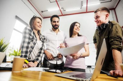 Gruppe von jungen Leuten am Tisch vor Laptop