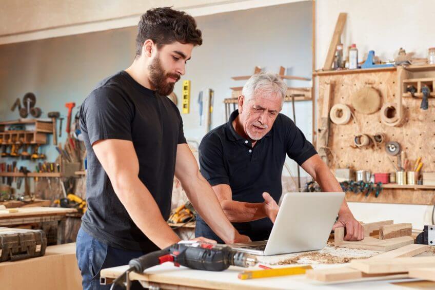 Zwei Handwerker vor einem Notebook / Laptop in einer Werkstatt