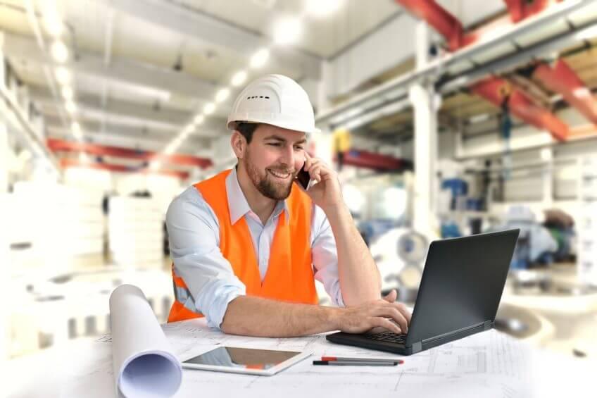 Industriearbeiter mit Helm und Warnweste vor Notebook