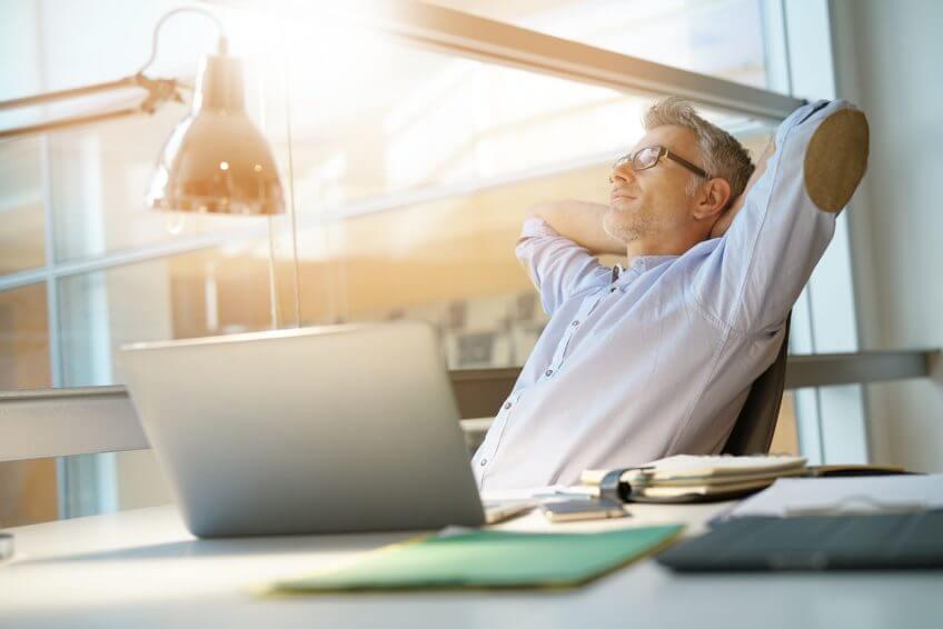 Mann im Büro freut sich entspannt über die wirksame Full Disk Encryption