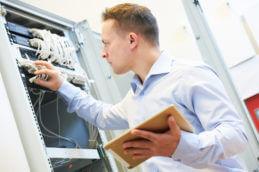 Fachinformatiker vor einem Serverschrank