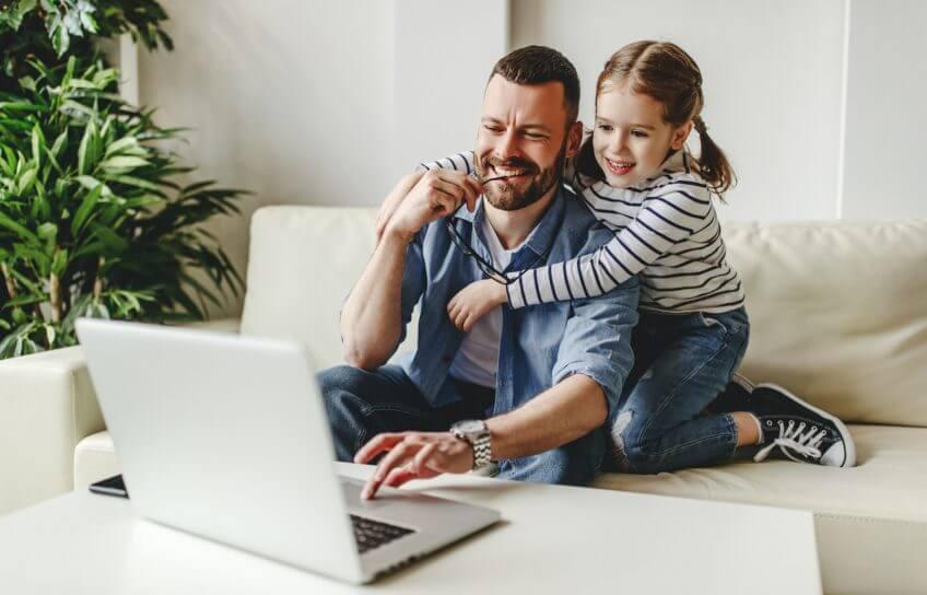Vater und Tochter im Homeoffice vor einem Laptop