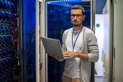 Junger IT-Techniker Fachinformatiker mit Notebook vor einem Netzwerkschrank