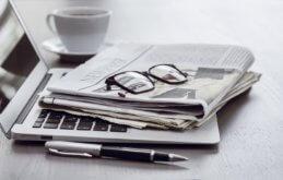 News und Neuigkeiten aus der IT Zeitungen auf einer Notebooktastatur