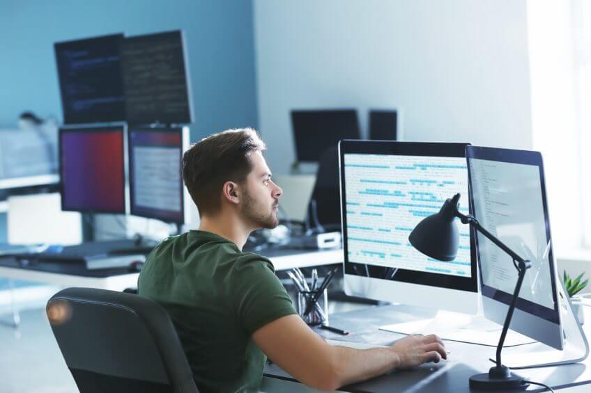 Mann arbeitet an Computern