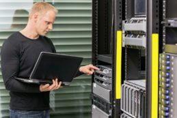 Techniker mit Notebook vor Rack Server